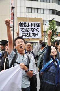 デモ行進とともにシュプレヒコールを叫ぶ人々